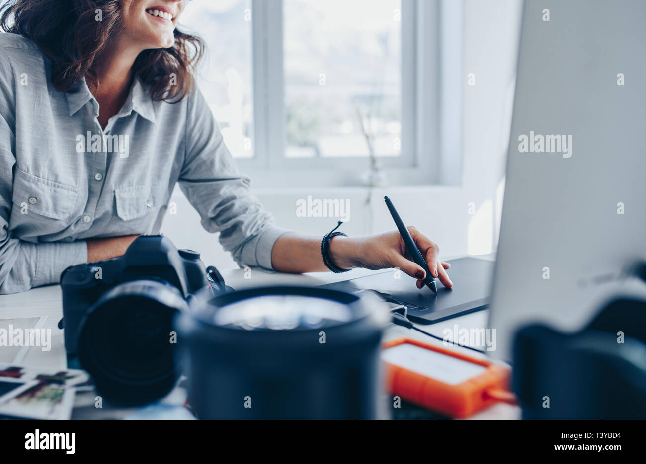 Female photographer working on computer using drawing pad at her desk. Young woman using graphic tablet and drawing pen to retouch the images. Stock Photo