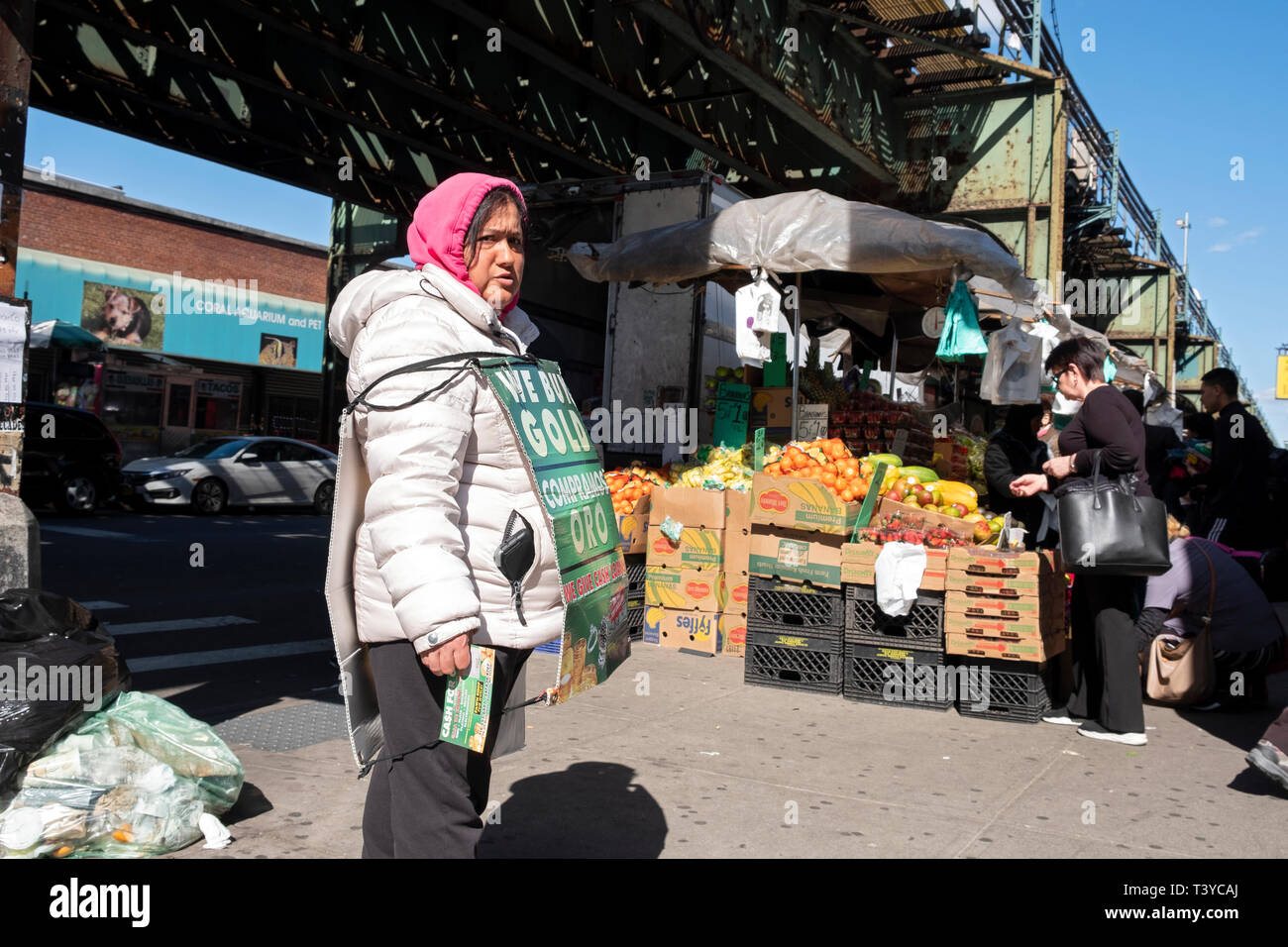 A Spanish speaking woman under the el wearing a sandwich board & giving out leaflets for a jeweler who want to buy gold. In Jackson Heights, Queens NY - Stock Image