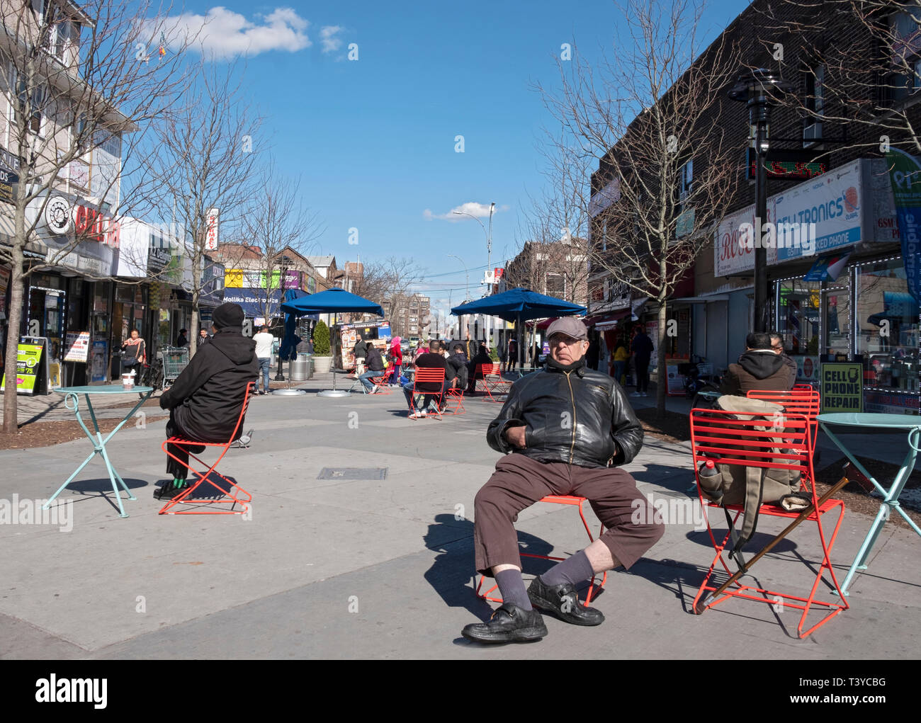 A middle aged man sits in a public space on 37th Road in Jackson Heights, Queens, New York City. - Stock Image