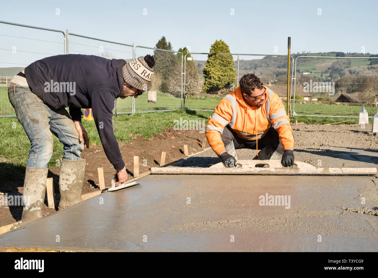 Presteigne, Powys, Wales, UK. Workmen using concrete floats to smooth the surface of a freshly laid concrete floor Stock Photo