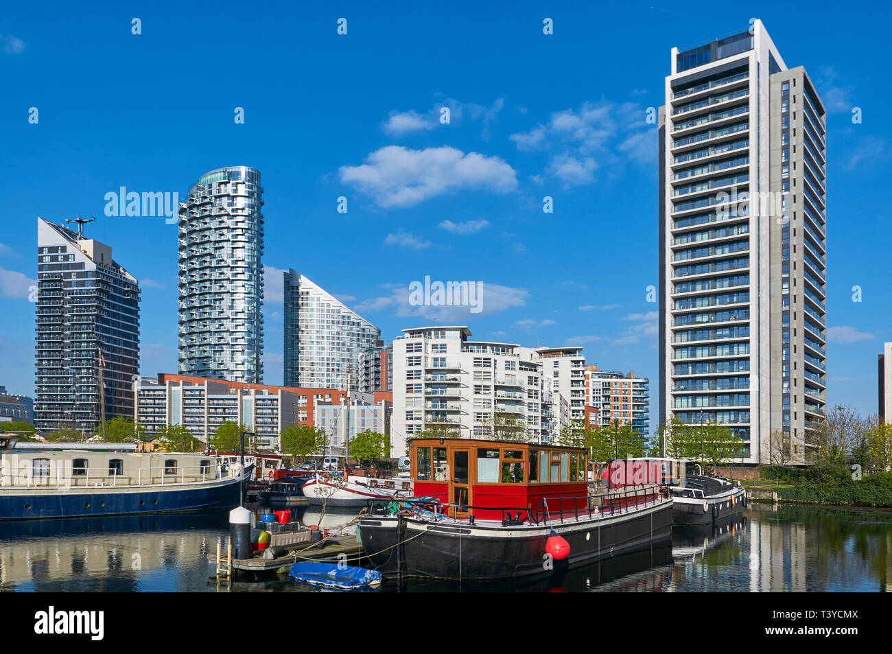 Poplar Dock Marina in London Docklands, with moored vessels and new apartment buildings - Stock Image