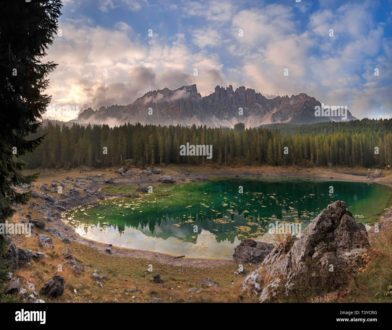 A gorgeous sunrise at the lake of Carezza, a wonderful lake surrounded by two of the most famous massifs  of the Italian Dolomites, the Catinaccio&Ros - Stock Image