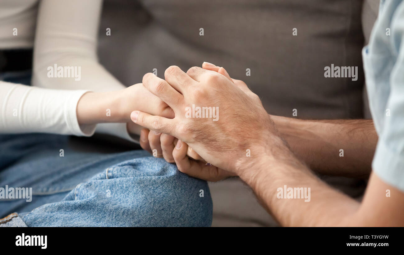 Close up couple in love holding hands, showing support, togetherness Stock Photo