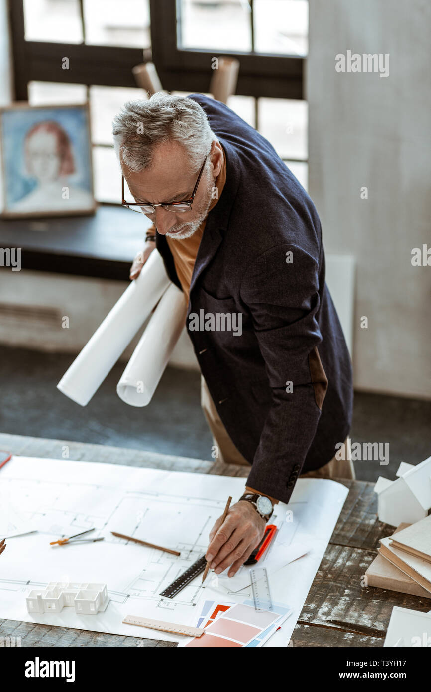 Finishing sketches. Grey-haired interior designer using rulers and pencils while finishing sketches - Stock Image
