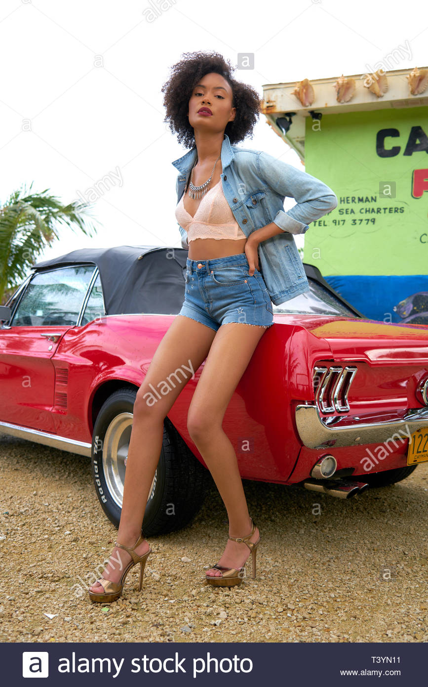 woman sitting on red Ford Mustang soft-top convertible coupe - Stock Image