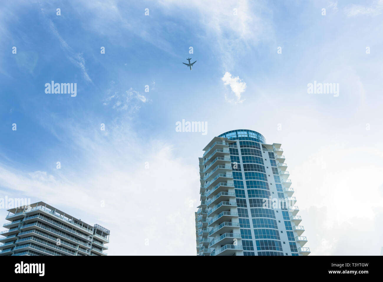 High-rise apartment buildings with passenger plane flying past high above - Stock Image