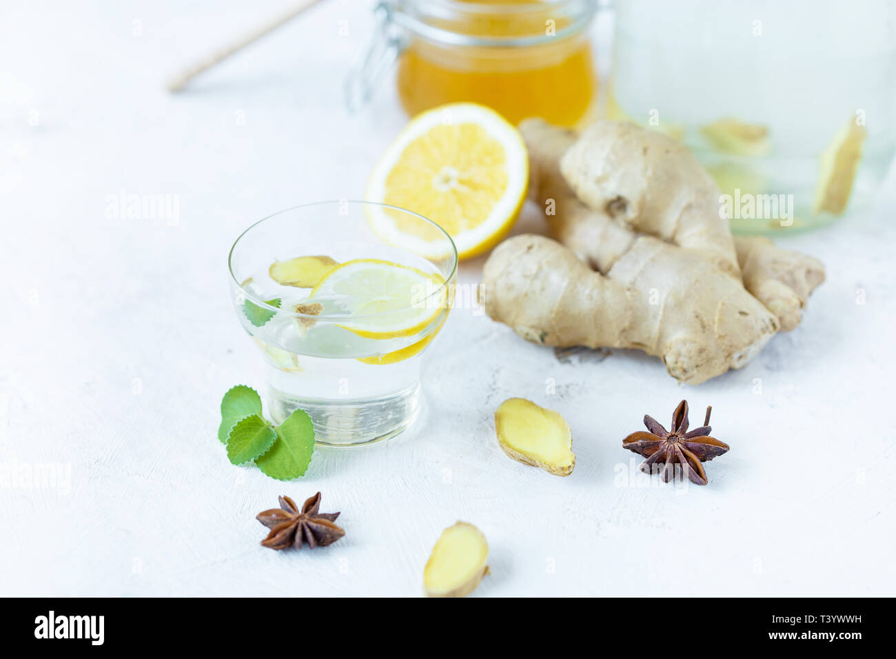 Healthy ginger drink in a cup. Ginger root, honey in a jar, lemon on a white table. Immune Cocktail Copy space - Stock Image