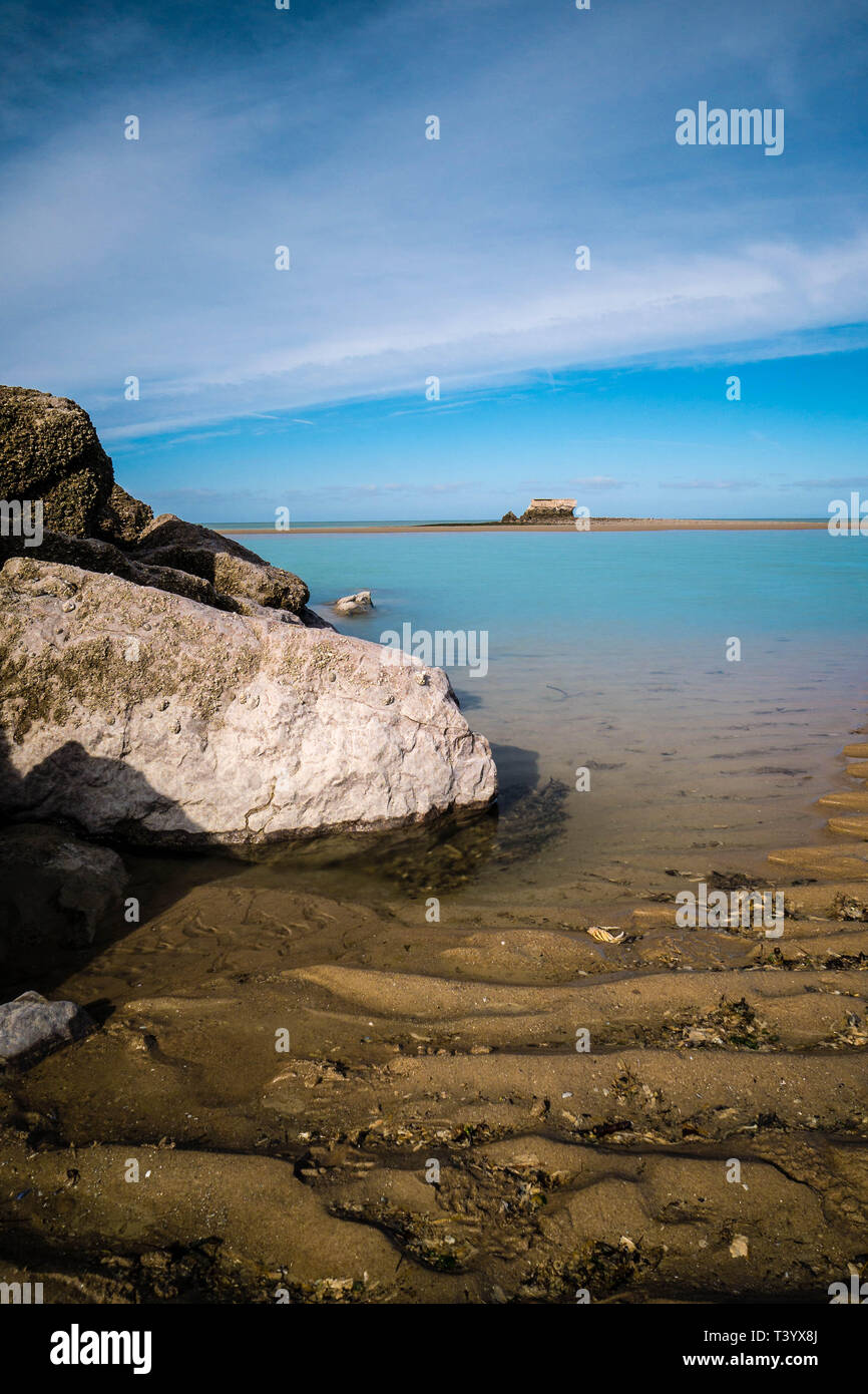 Ancient Fort de l'Heurt in the distance on the waterline with rocks in the foreground - Stock Image