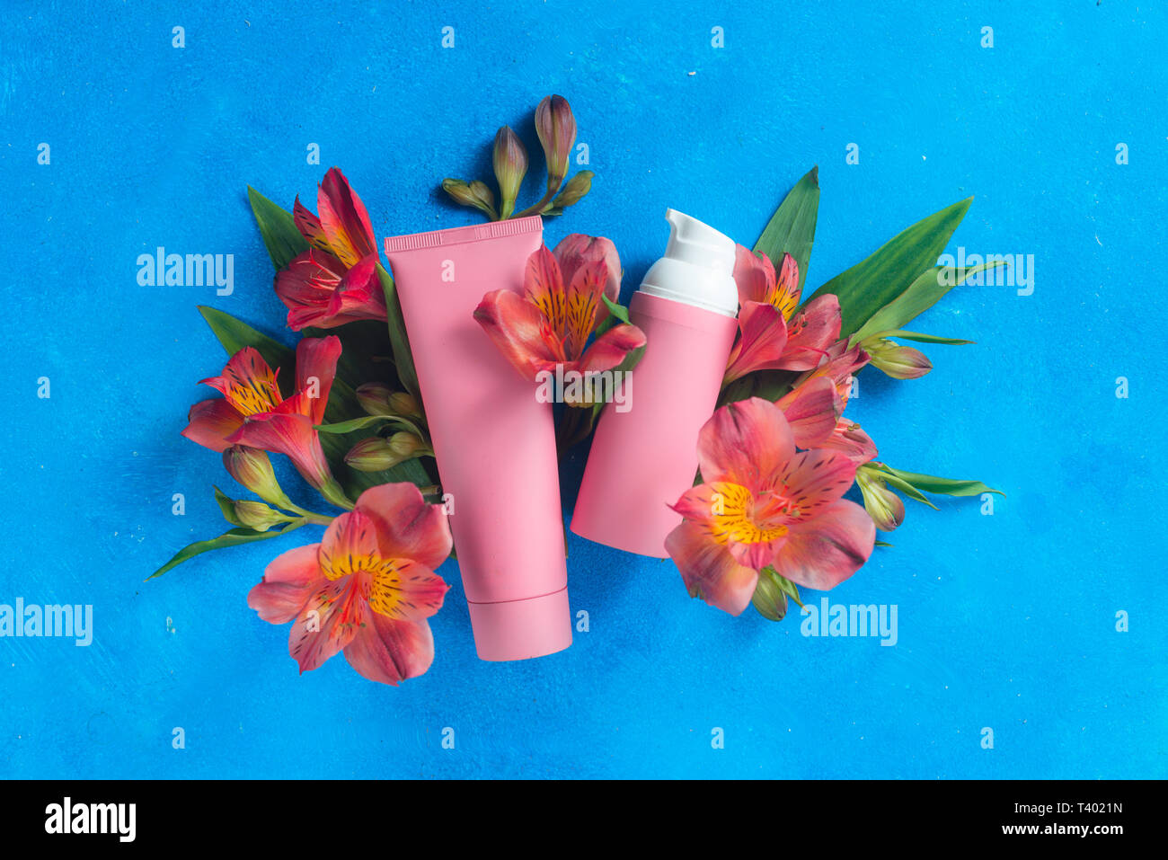 Skin care cosmetics in pink palette in on a blue background with spring flowers. Natural cosmetics conceptual flat lay with copy space Stock Photo