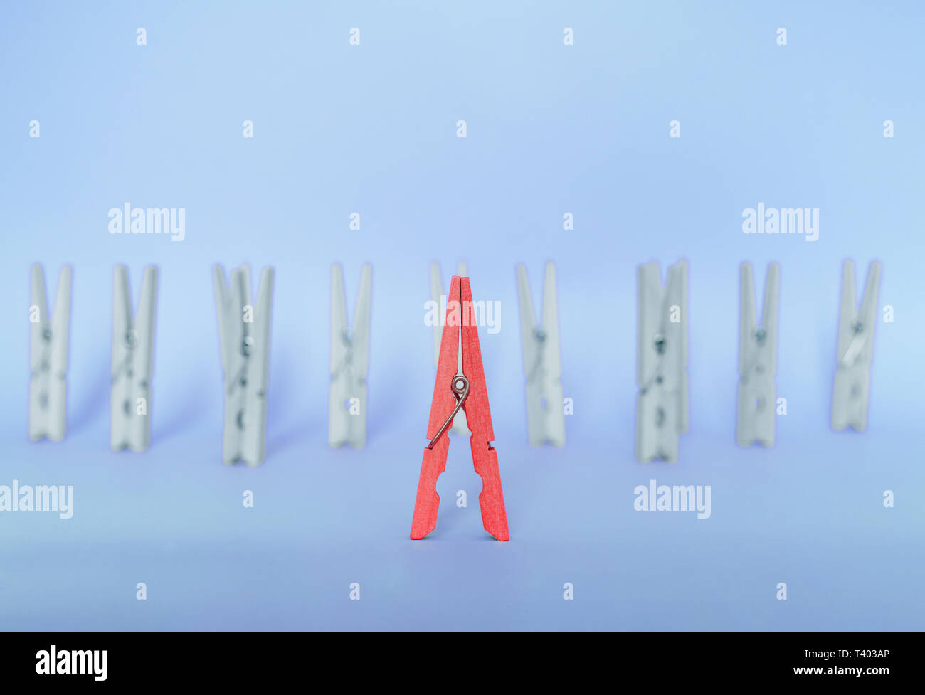 Unique, individuality, outstanding,leadership and think different concept. Red wooden clip stand out of colorless clips on blue backgrounds Stock Photo