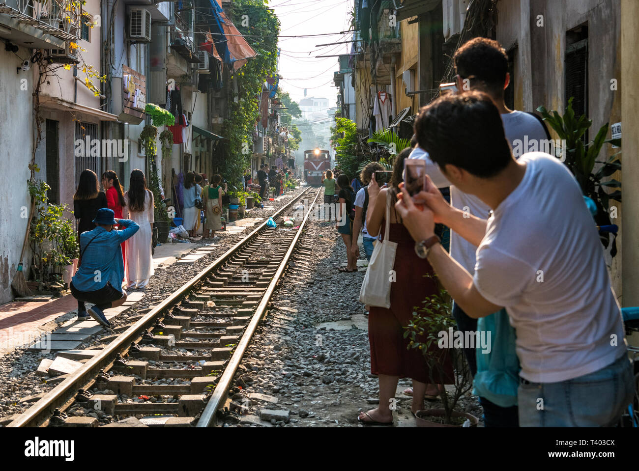 """Train street"" in Hanoi, where twice a day a speeding train passes only centimetres away from the homes of this residential neighbourhood, Vietnam - Stock Image"