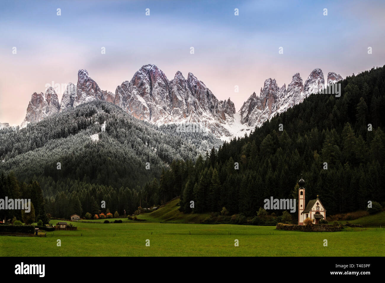 The famous chappel of Sankt Johann in Ranui in the val di Funes (Dolomites) with the jagge peaks of the Odle range in the background - Stock Image