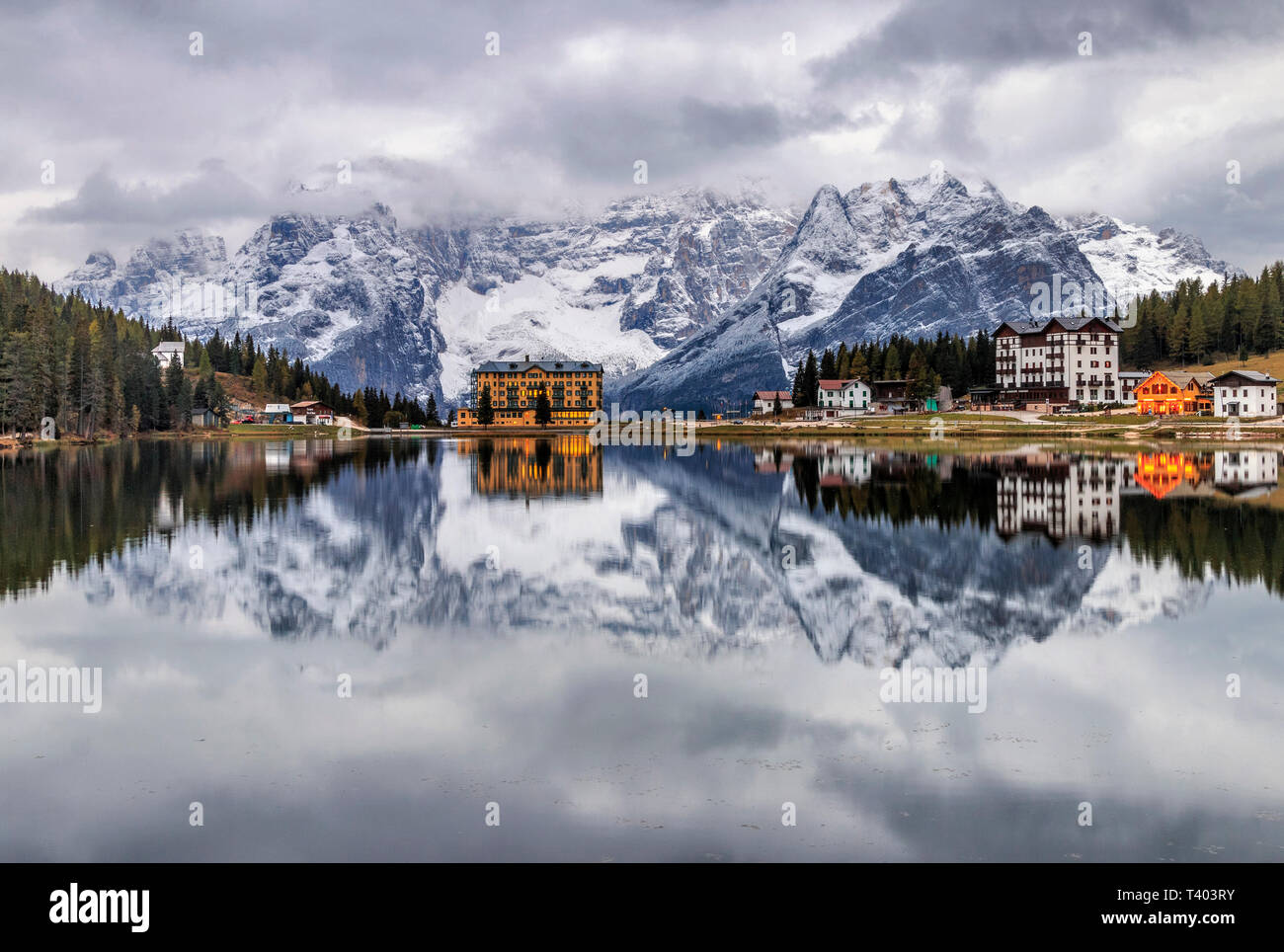 A tranquil view at sunrise of the Lake of Misurina, a lake in the Dolomiti d'Ampezzo, not far from the town of Cortina, with the majestic rocky walls  - Stock Image