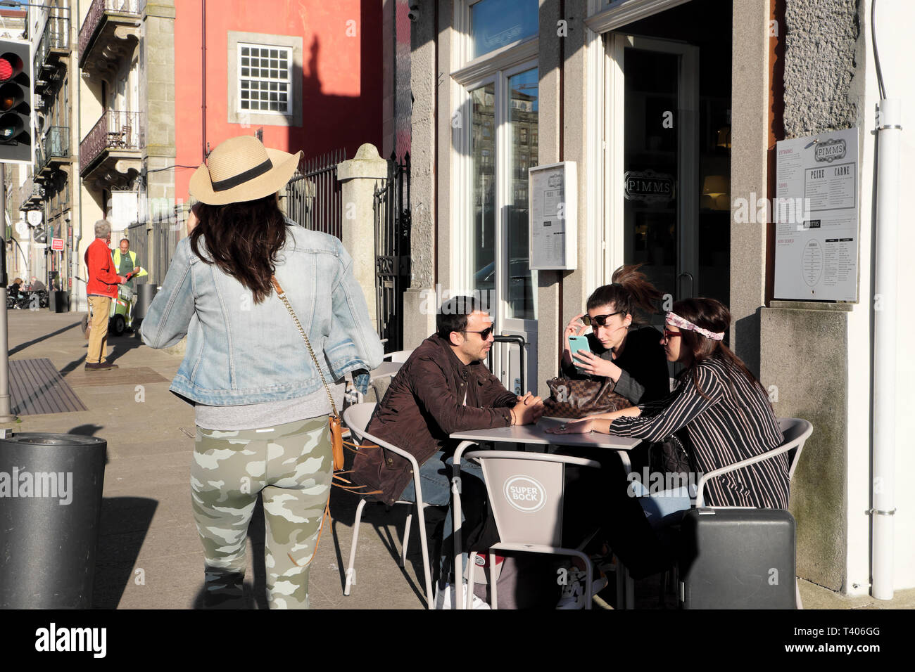 Group of friends customers sitting outside at a cafe restaurant table in the street in Porto, Portugal Europe EU   KATHY DEWITT Stock Photo