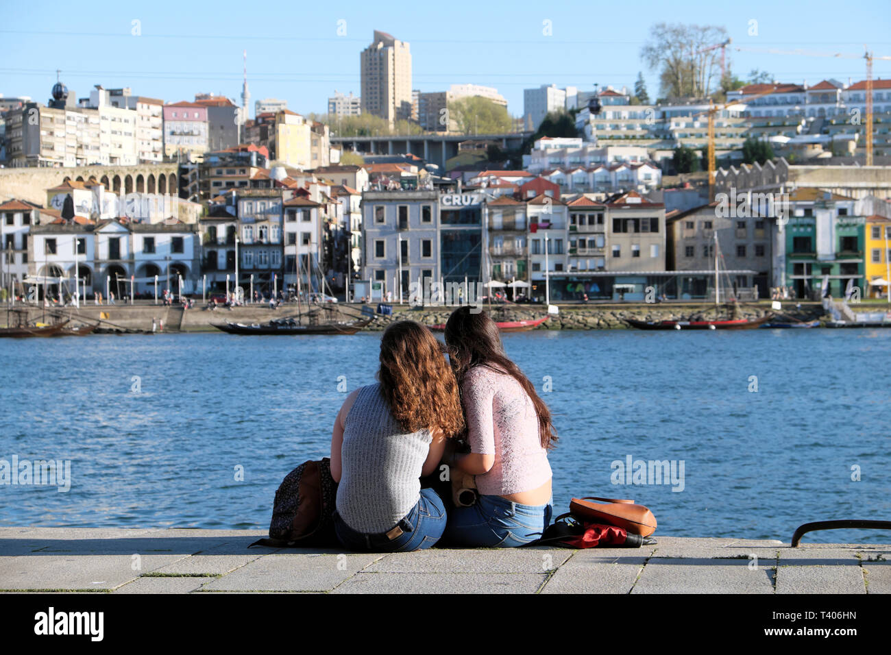 Two young women sitting together eating on the quay looking across the Douro River at Vila Nova de Gaia in Porto, Portugal Europe   KATHY DEWITT Stock Photo