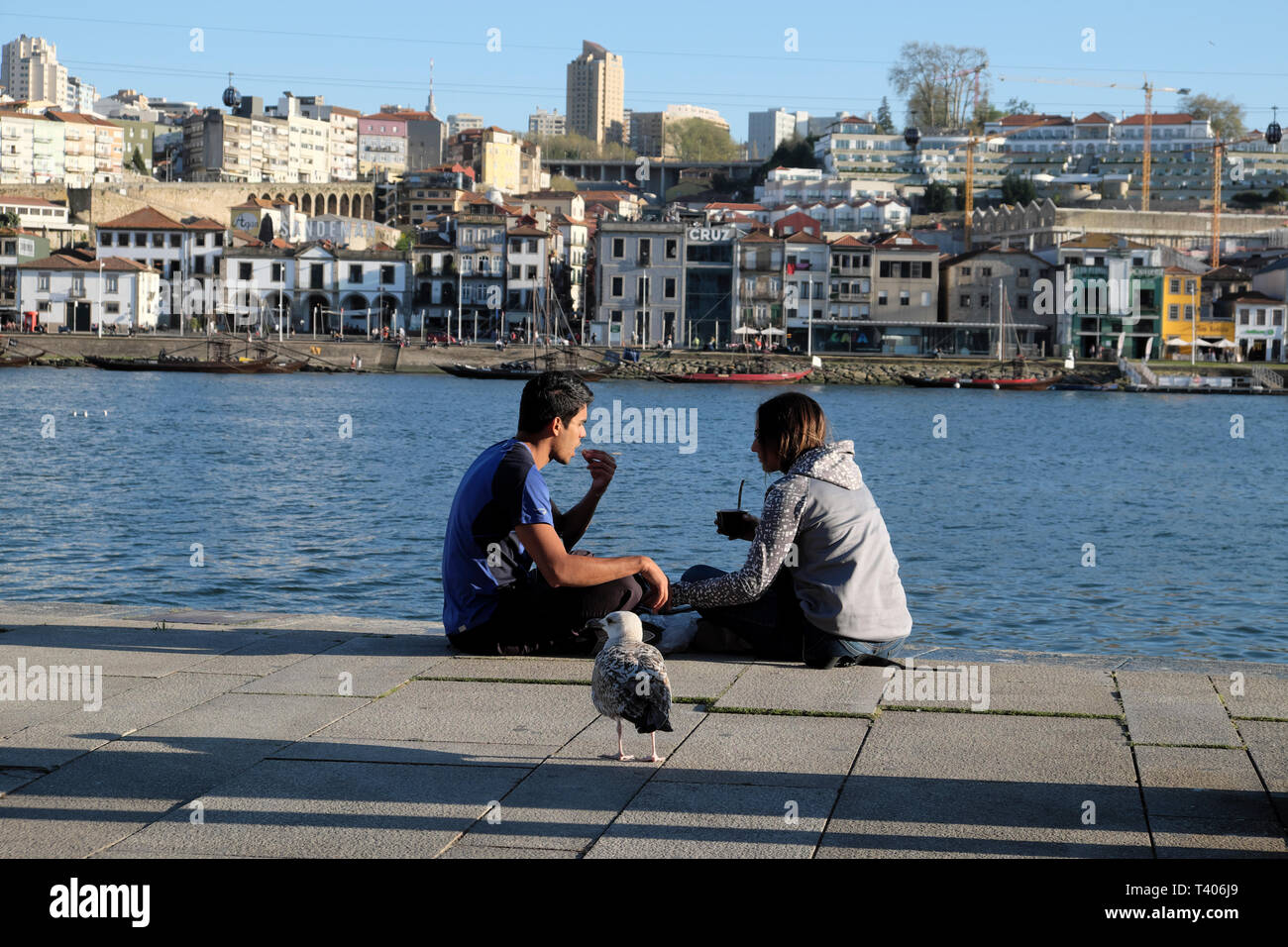 A young couple sitting together eating on the quay by the Douro River on a spring afternoon in the city of Porto, Portugal Europe   KATHY DEWITT Stock Photo