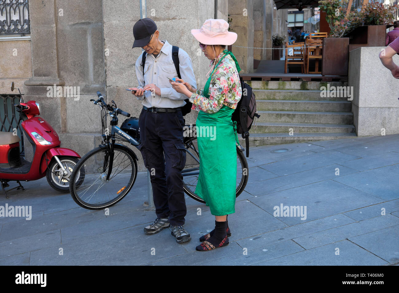 An older Japanese couple navigating the streets of Porto with maps on their mobile phones in a street in Portugal Europe   KATHY DEWITT Stock Photo