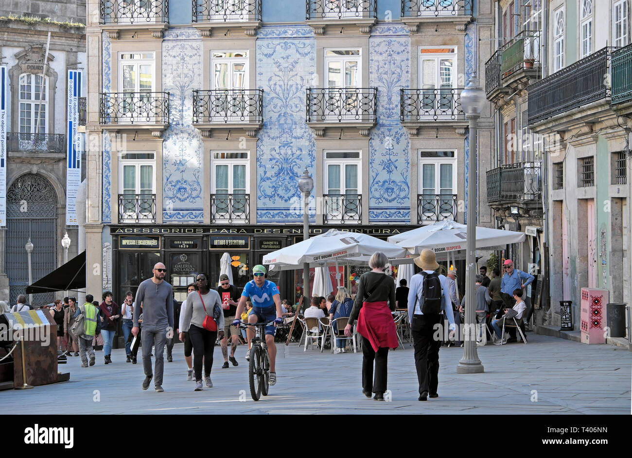 Cyclist riding bike along Rua das Flores past building with blue azulejos tiles, restaurant and tourists in street Porto Portugal Europe  KATHY DEWITT - Stock Image
