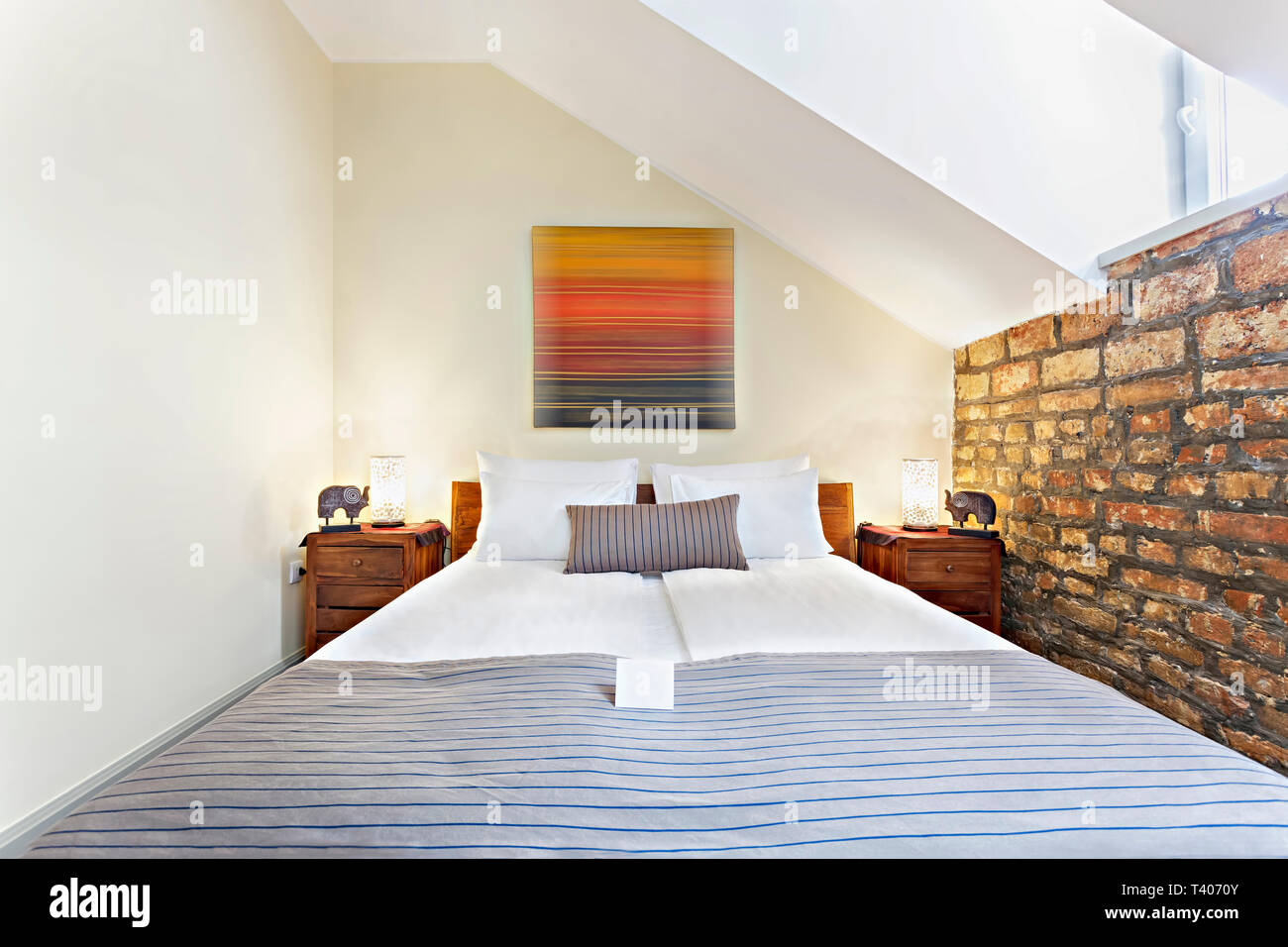 Bedroom interior in luxury loft, attic, apartment with roof windows - Hotel room - vacation concept background Stock Photo