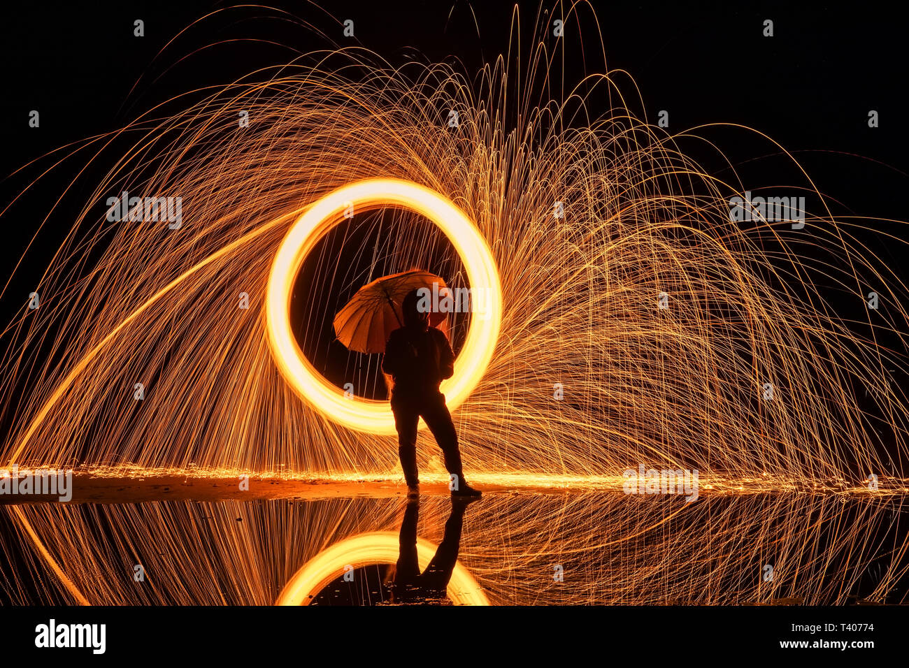 Light painting. Pyrotechnic display at night with the reflection of the water Stock Photo