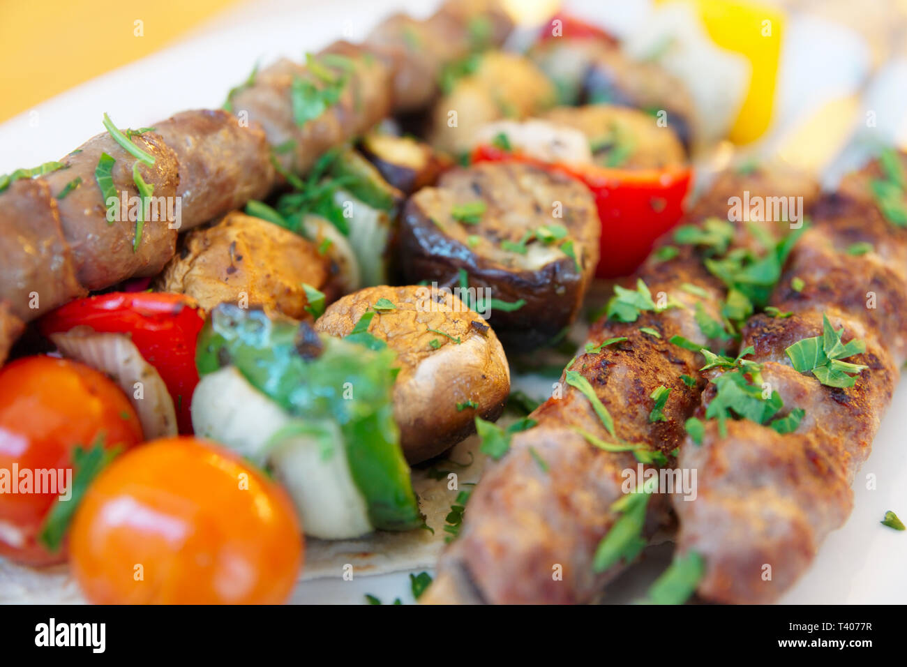 Grilled chicken hearts and vegetables on the metal skewers - Stock Image
