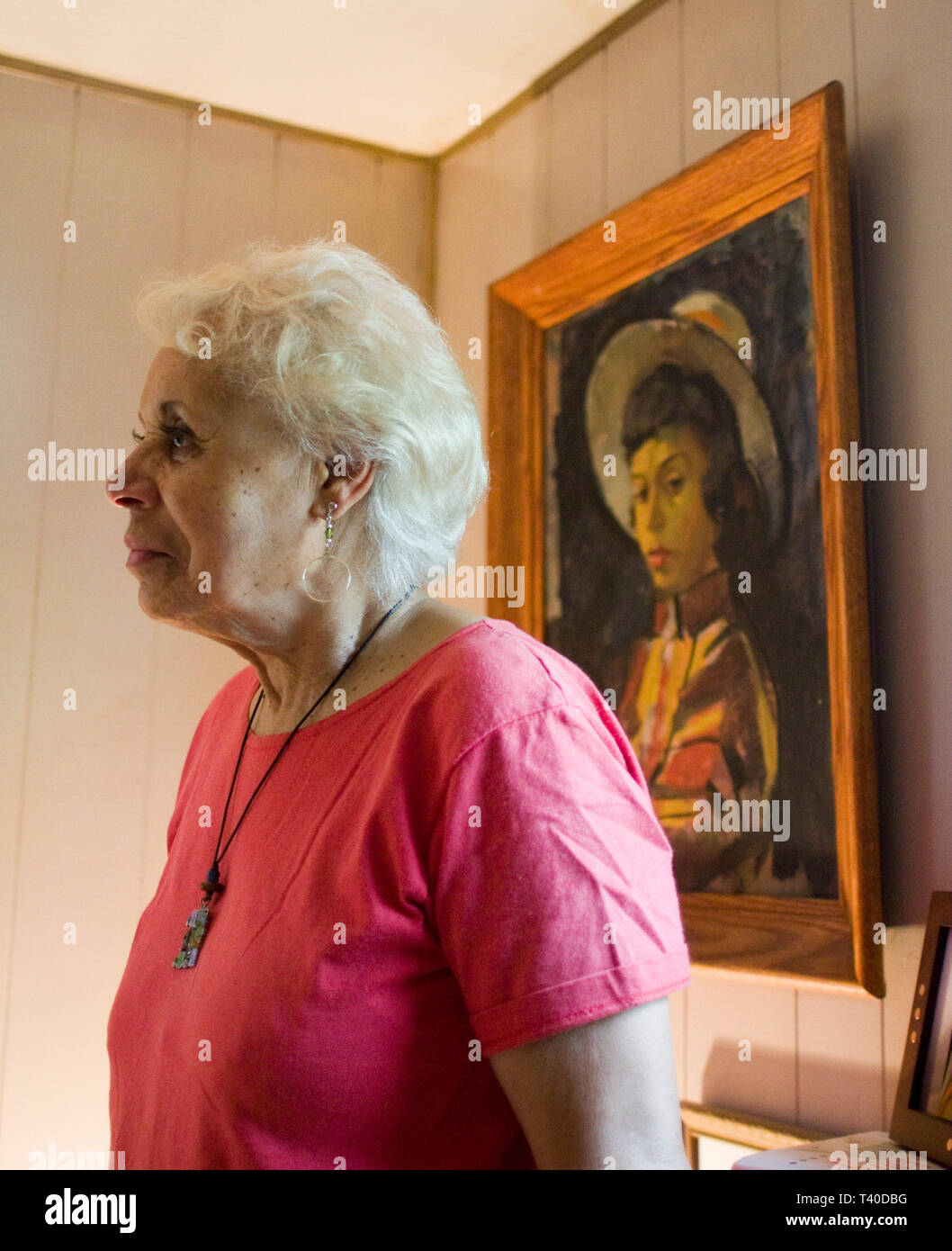 senior African American woman in her home in front of a painting of herself as a younger woman - Stock Image