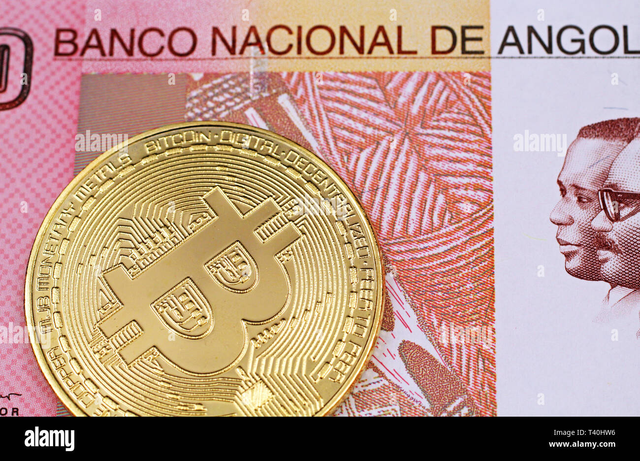 A macro image of a physical, golden Bitcoin with a colorful one hundred Angolan kwanza bank note close up - Stock Image