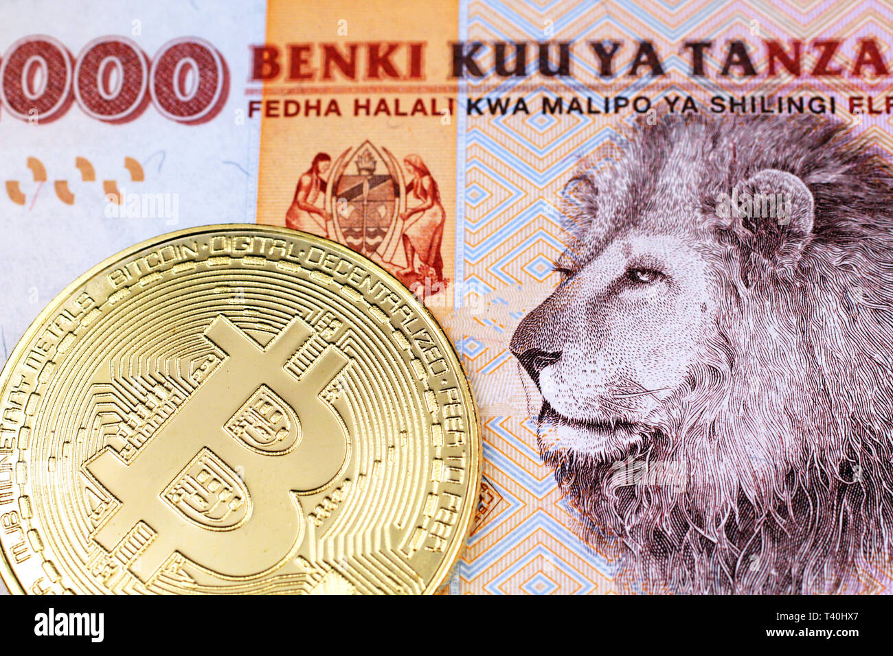 A close up image of an orange, Tanzanian two thousand shilling note with a shiny, gold physical bitcoin in macro - Stock Image
