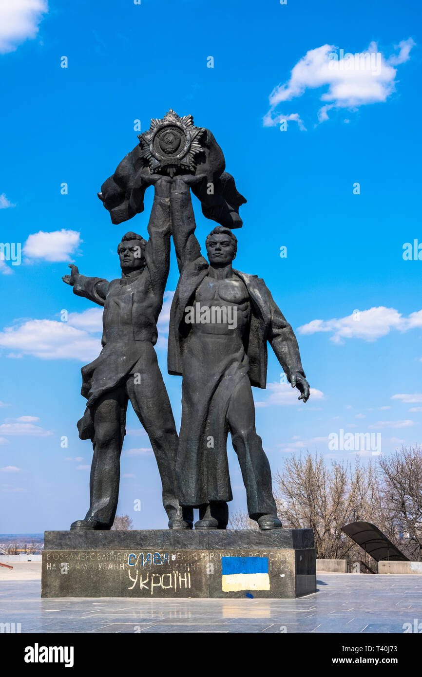 Bronze statue depicting a Russian and Ukrainian workers holding up the Soviet Order of Friendship of Peoples near the People's Friendship Arch (Kiev/U - Stock Image