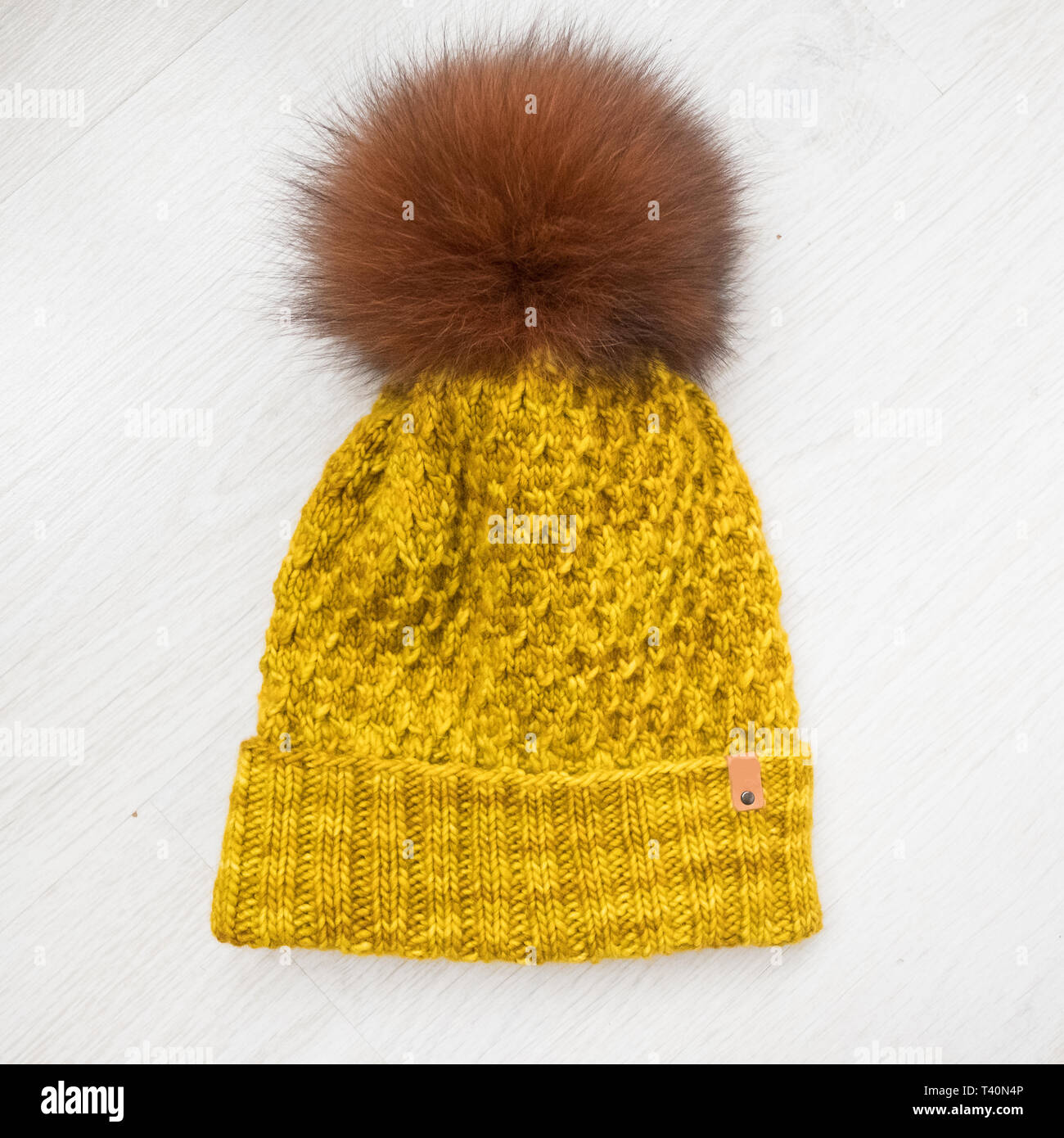 handmade knit hats with fur pompom on white background - Stock Image