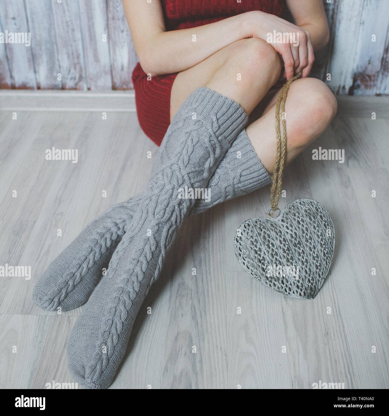 Cozy winter evening , warm woolen socks. Woman relaxing at home. Comfy lifestyle. - Stock Image