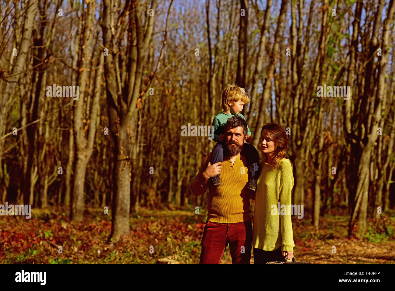 Mother and father holding little child on shoulder walk in spring park, family values. Family values concept. Circle of love and strength - Stock Image