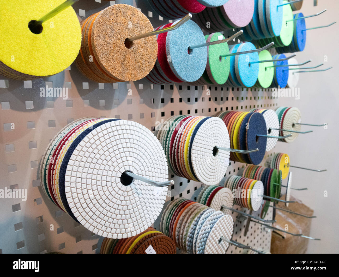 closeup many different polishing and grinding replaceable disks for industrial power tools hanging on stand at hardware equipment market - Stock Image