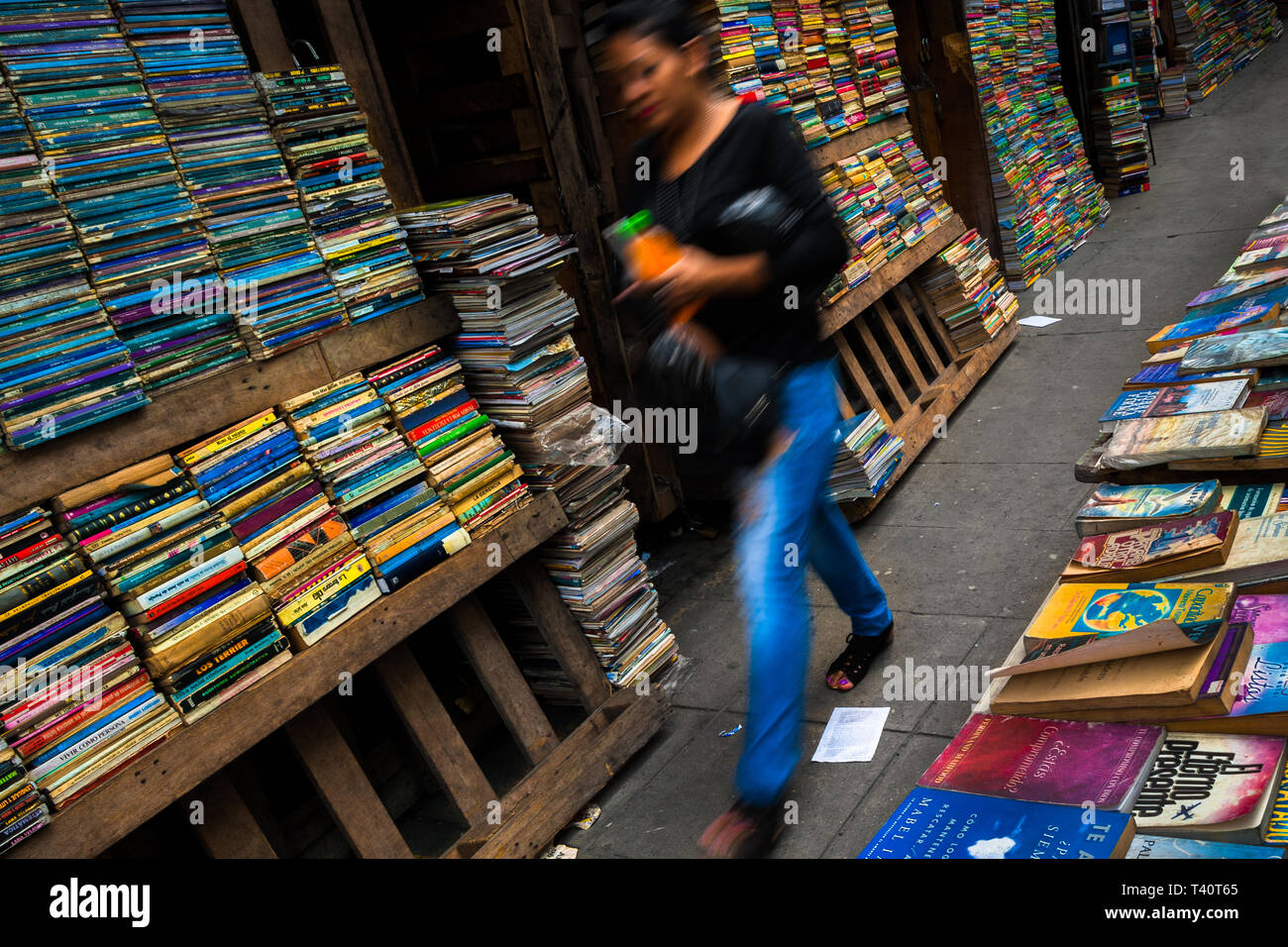 A Salvadoran woman walks along hundreds of used books stacked in shelves on the street in a secondhand bookshop in San Salvador, El Salvador. - Stock Image