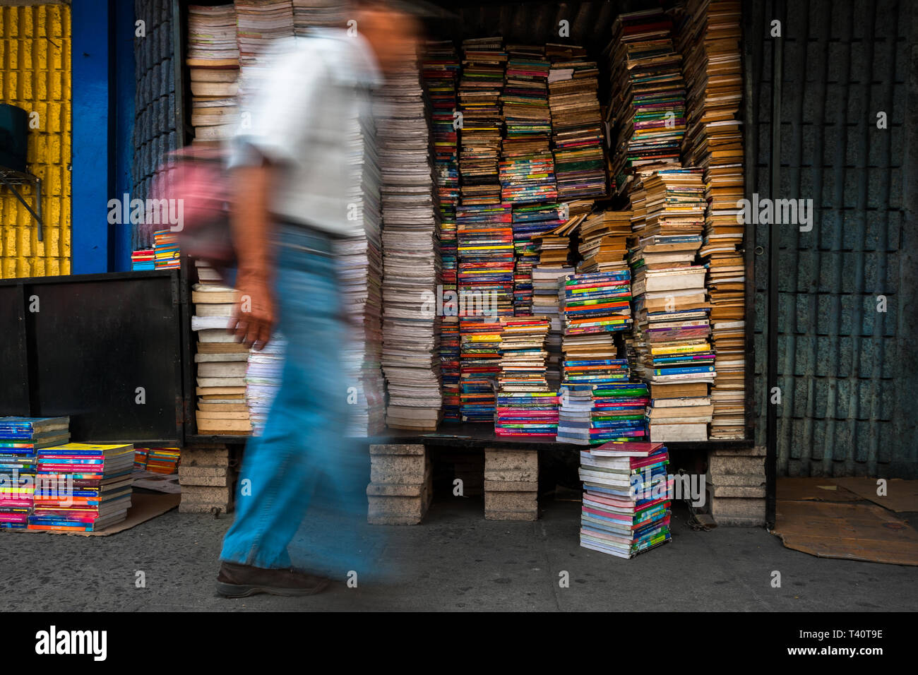 A Salvadoran man walks in front of piles of used books stacked in a box on the street in a secondhand bookshop in San Salvador, El Salvador. Stock Photo
