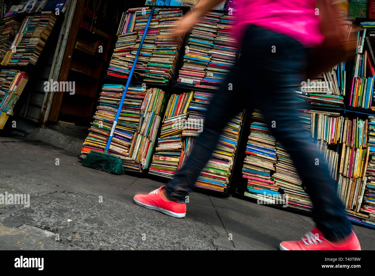 A Salvadoran woman walks along hundreds of used books stacked in boxes on the street in a secondhand bookshop in San Salvador, El Salvador. Stock Photo