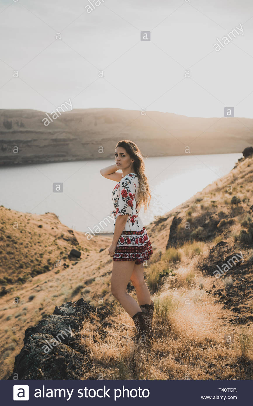 woman wearing white and multicolored floral minidress standing on hill across lake during daytime - Stock Image