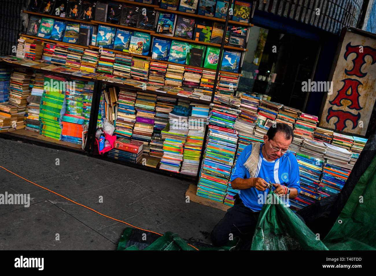 A Salvadoran bookseller works in front of piles of used books stacked on the street in a secondhand bookshop in San Salvador, El Salvador. - Stock Image