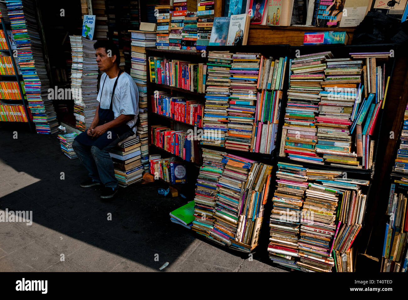 A Salvadoran bookseller sits in front of stacks of used books piled on the street in a secondhand bookshop in San Salvador, El Salvador. - Stock Image