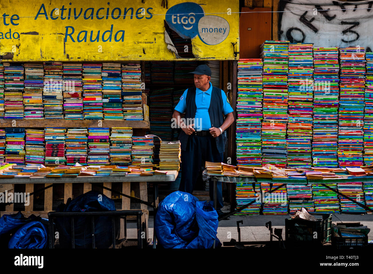 A Salvadoran bookseller stands in front of piles of used books stacked on the street in a secondhand bookshop in San Salvador, El Salvador. - Stock Image