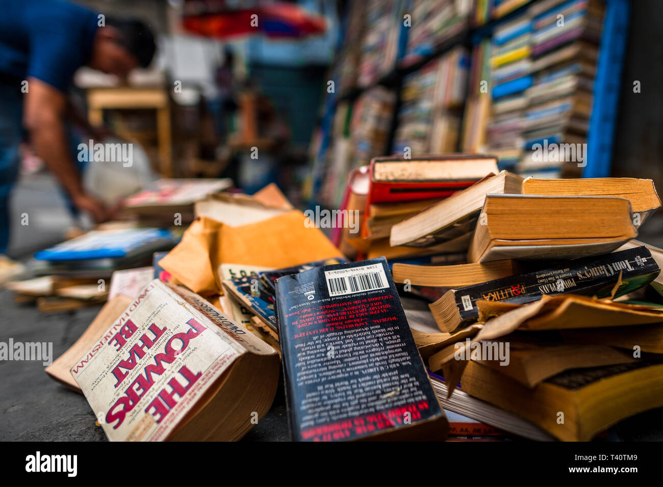 Used books are seen lying disorganized on the street in a secondhand bookshop in San Salvador, El Salvador. - Stock Image