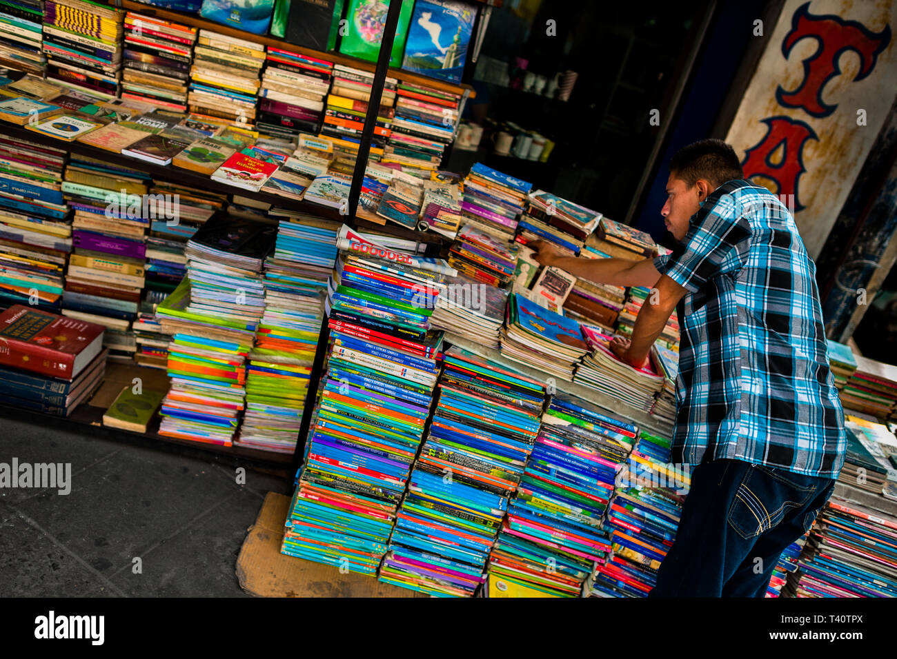 A Salvadoran bookseller arranges piles of used books stacked on the street in a secondhand bookshop in San Salvador, El Salvador. - Stock Image