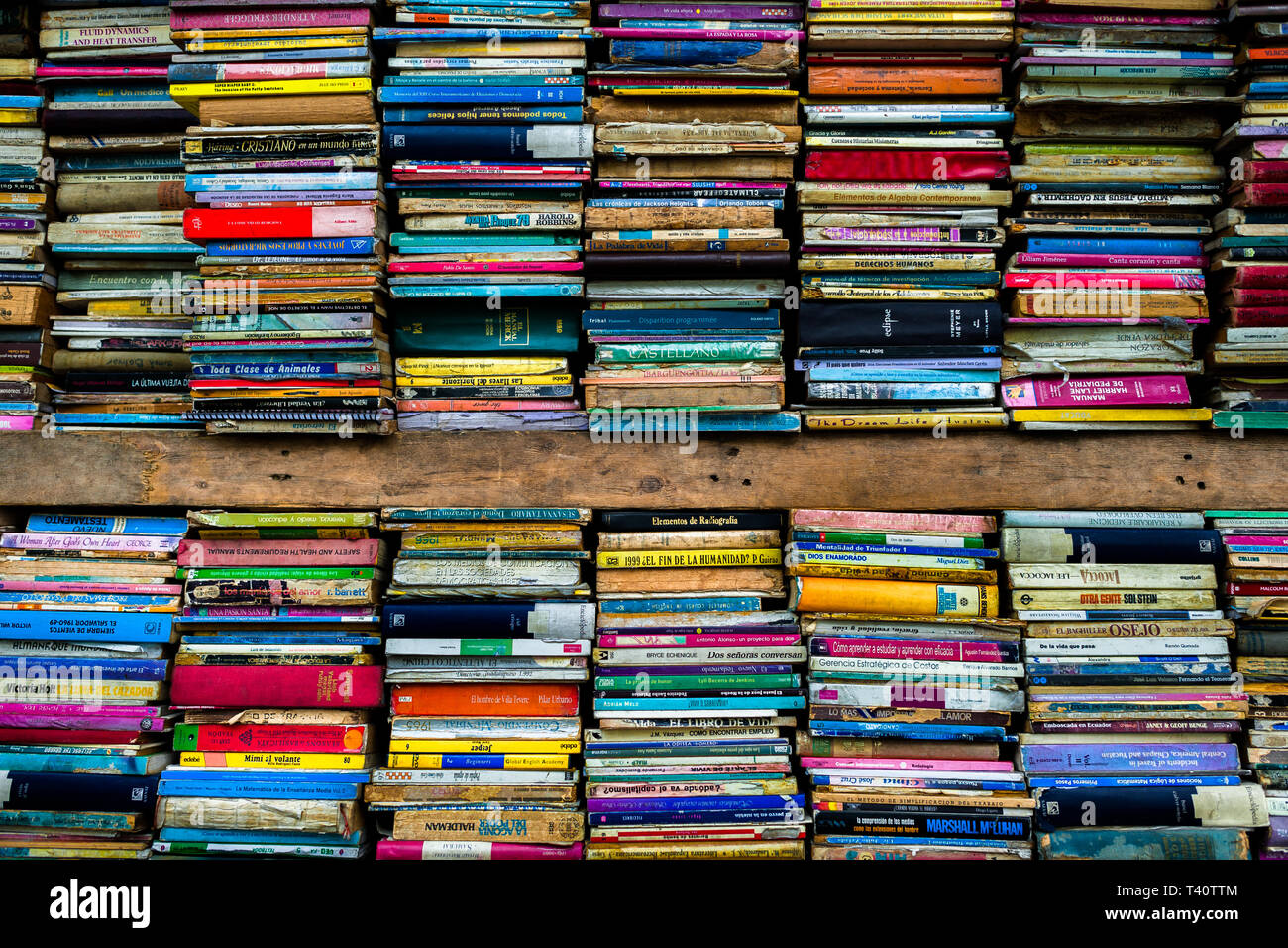 Spines of used books are seen stacked in shelves in a secondhand bookshop in San Salvador, El Salvador. - Stock Image