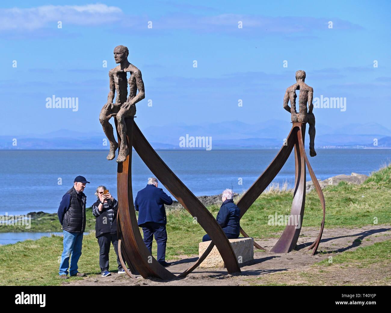 Visitors at 'Ship', metal sculpture by Anna Gillespie, 2019. Half Moon Bay, Heysham, Lancashire, England, United Kingdom, Europe. - Stock Image