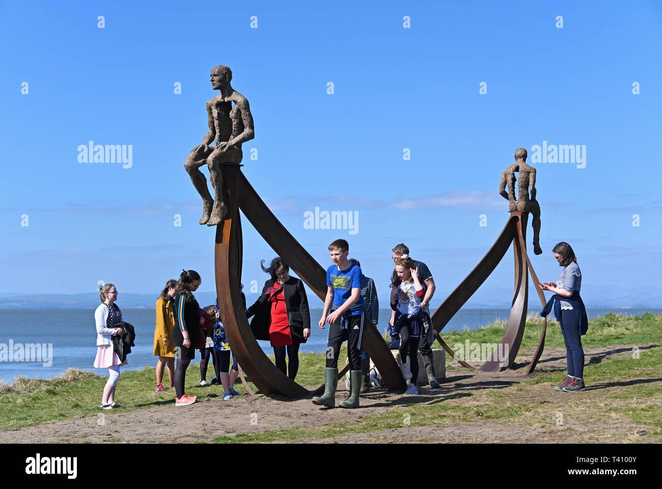 Party of children at 'Ship', metal sculpture by Anna Gillespie, 2019. Half Moon Bay, Heysham, Lancashire, England, United Kingdom, Europe. - Stock Image
