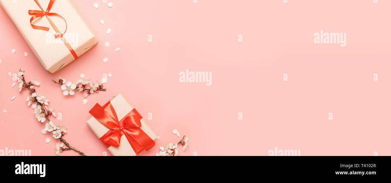 Valentines day, mothers day, womens day concept. Gift box with red bows and flowers on a pink background.Flat lay, top view, copy space - Stock Image