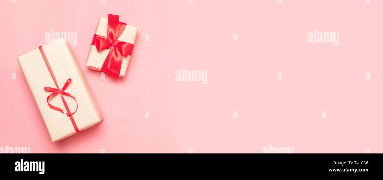 Valentines day, mothers day, womens day concept with copy space. Gift box with red bows on a pink background. - Stock Image