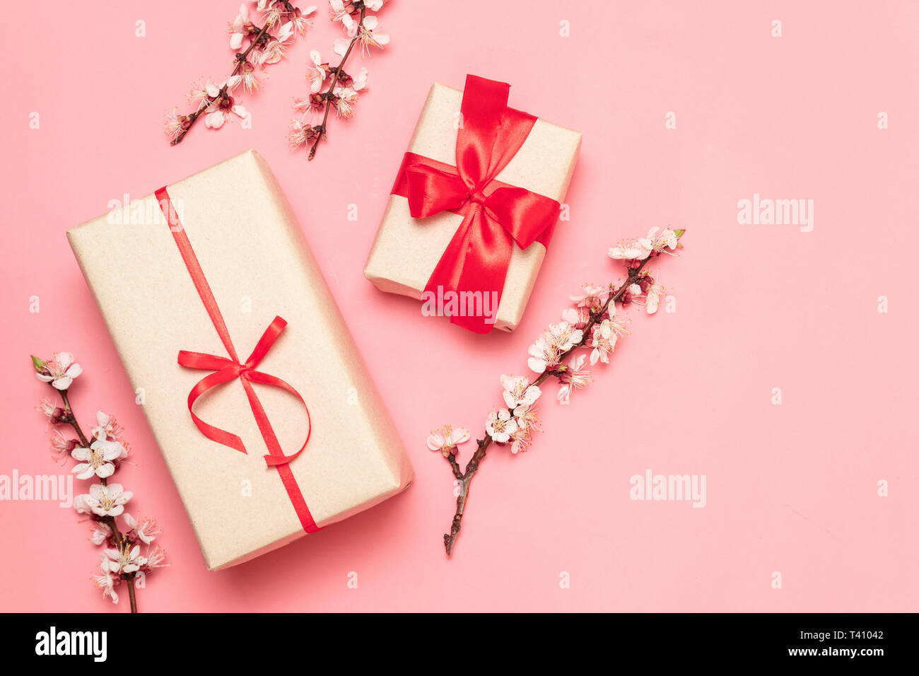 Mothers day, womens day concept. Gift box with red bows and flowers on a pink background. Flat lay, top view, copy space - Stock Image