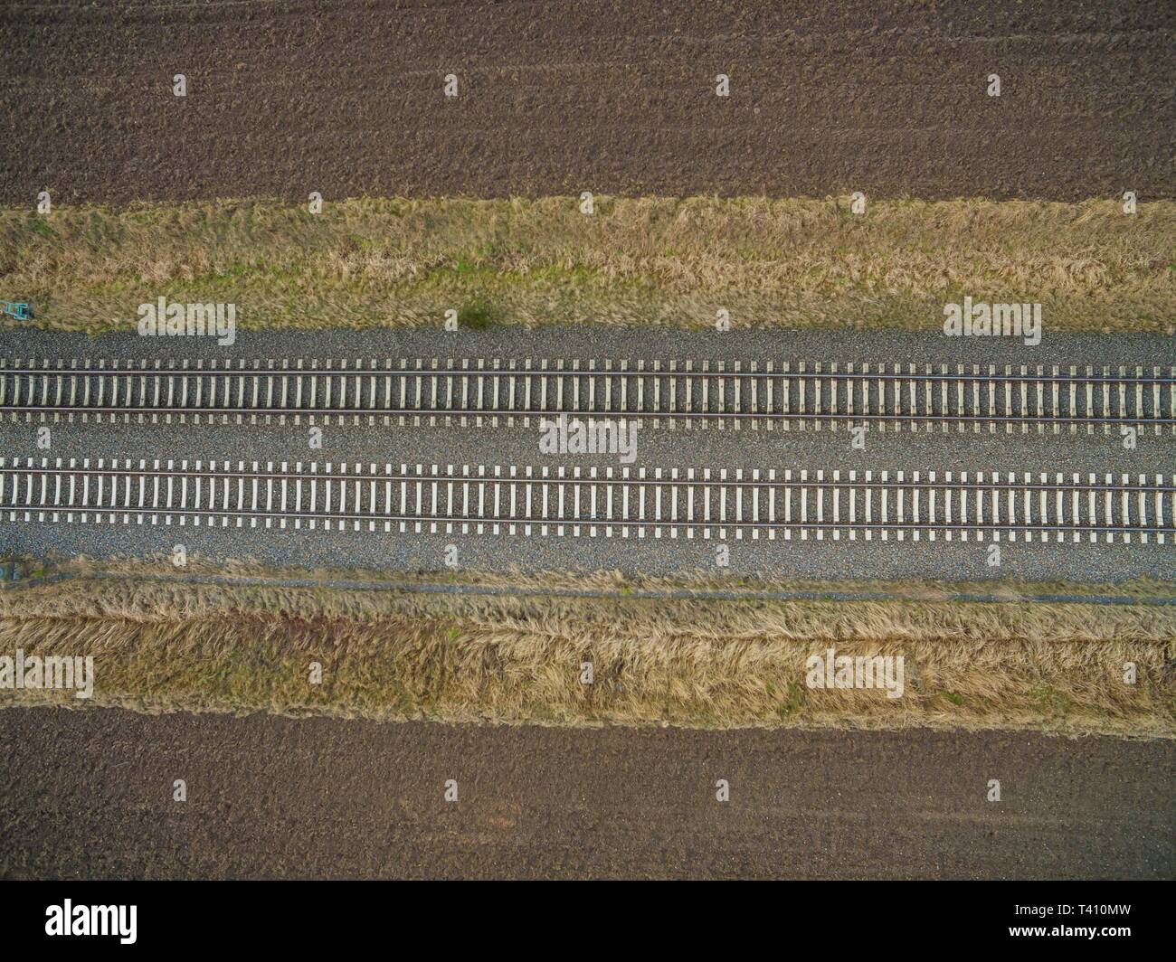 aerial view of railroad tracks in the backcountry between freshly plowed farmland - top view of the train tracks - Stock Image