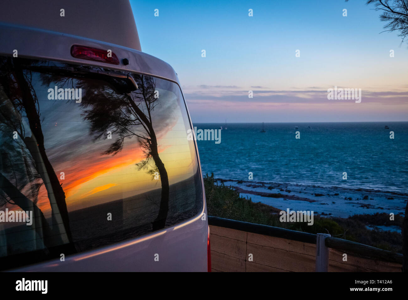 7cdd204af7 Reflection of tree silhouettes on campervan window in front of Indian Ocean  in Australia - Stock